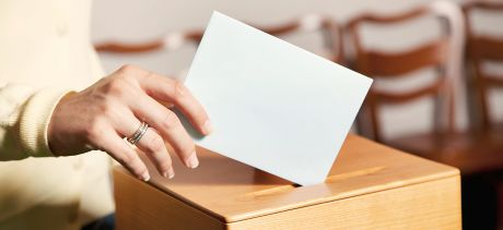 Hand putting ballot paper in box